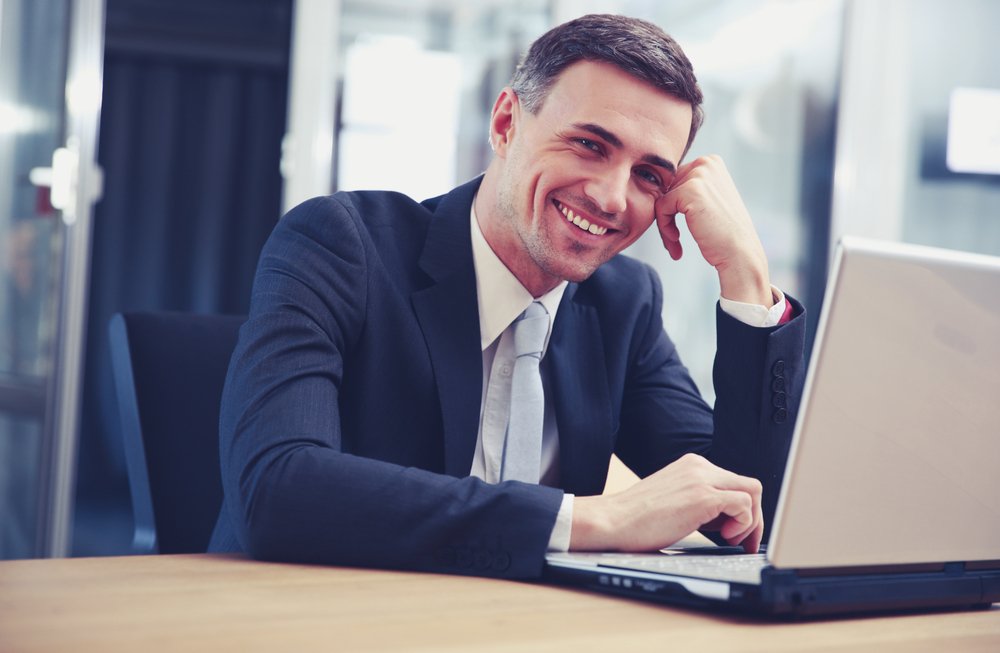 Cheerful businessman sitting with laptop at office