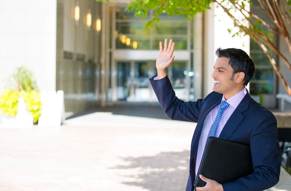 Closeup portrait of handsome happy smiling businessman in suit standing outside of his corporate company building,waving to a person he has to meet on a sunny day,isolated on a city urban background