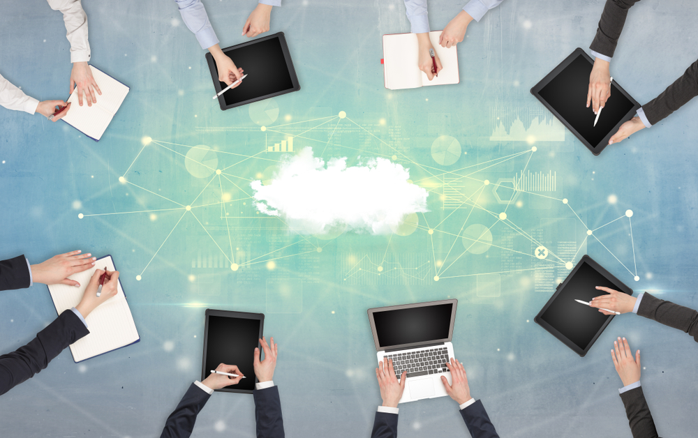 Group of people with devices in hands working on reports with online teamwork and cloud technology concept
