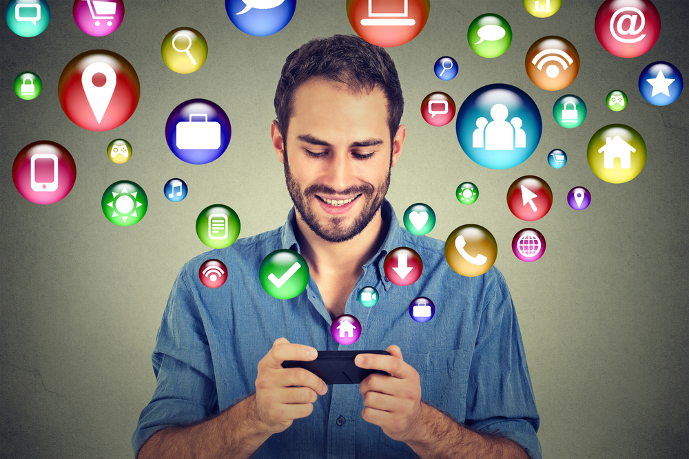 communication technology mobile phone high tech concept. Happy man using texting on smartphone social media application icons flying out of cellphone isolated grey wall background. 4g data plan-2